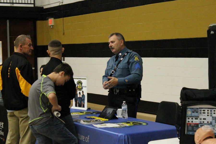 Students and teachers visit the table sponsored by the Missouri State Highway Patrol.