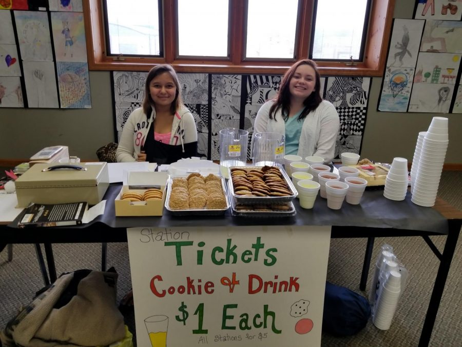 Kody Gilmore and Aalihya Wehner welcome art show attendees with cookies and other refreshments.