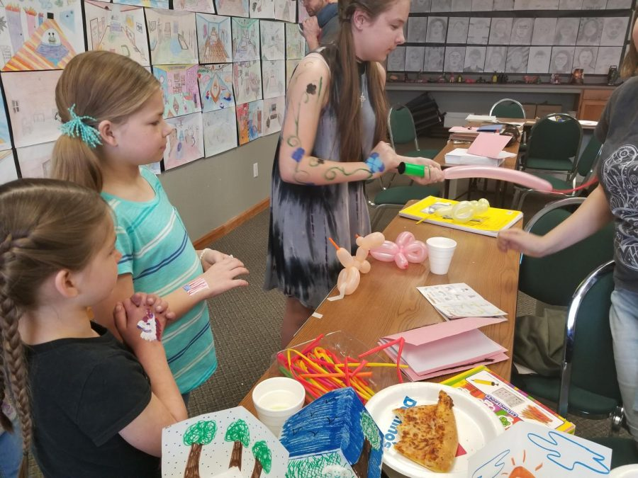 Local kids patiently wait while Mrs. Mories daughter makes fun animal balloons for them