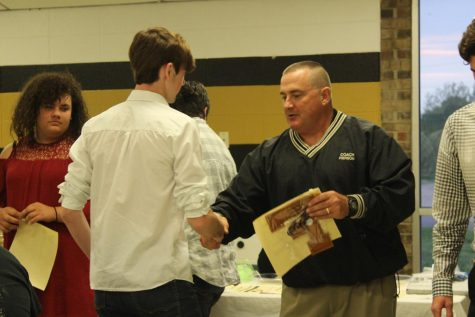 Patrick Sikes receives an award from Coach Pierson