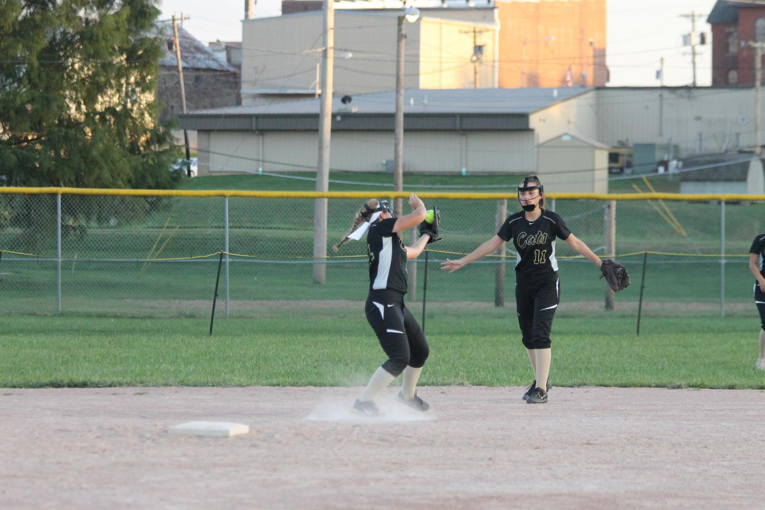 Kylee Bastie catching the ball with the help of Mackenzie Phillips.