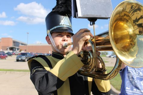 Freshman Jacob Yount warms up for the parade at the Jackson Marching Band Festival