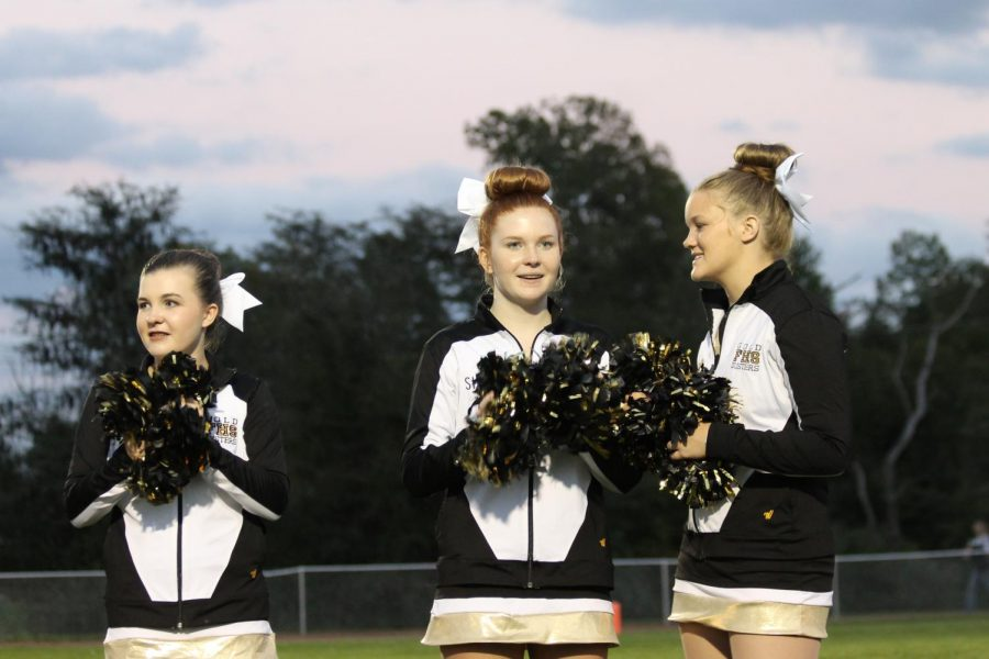 Freshman Paxton Clark and sophomores Stella Steck and Maddie Jennings prepare to greet the football players as they run out of the tunnel at the De Soto homecoming game.