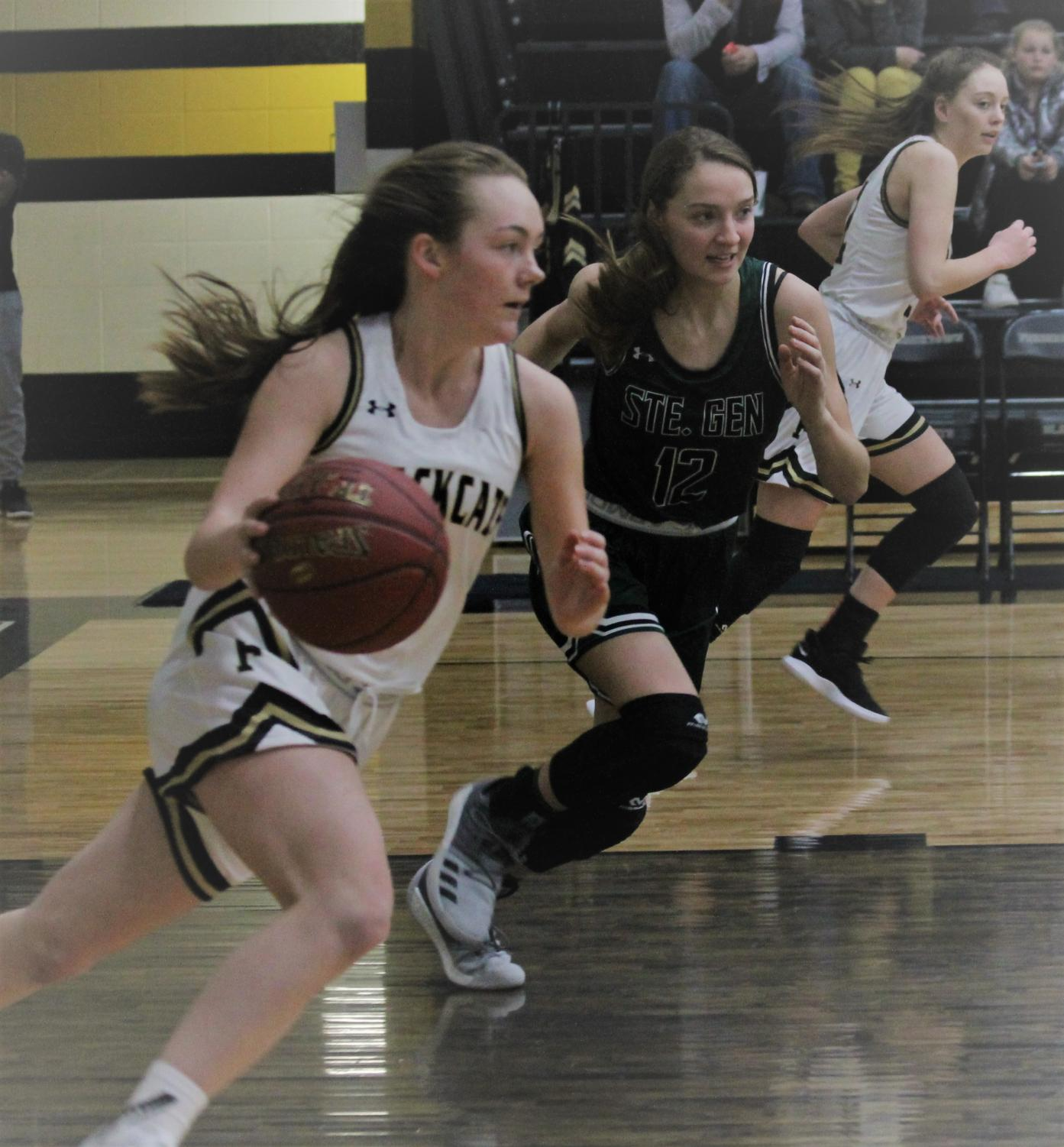 Mallory Mathes, Junior dribbles the ball to the other side of the court after a rebound.  Senior Maddie Burrows remains ready to receive a pass.