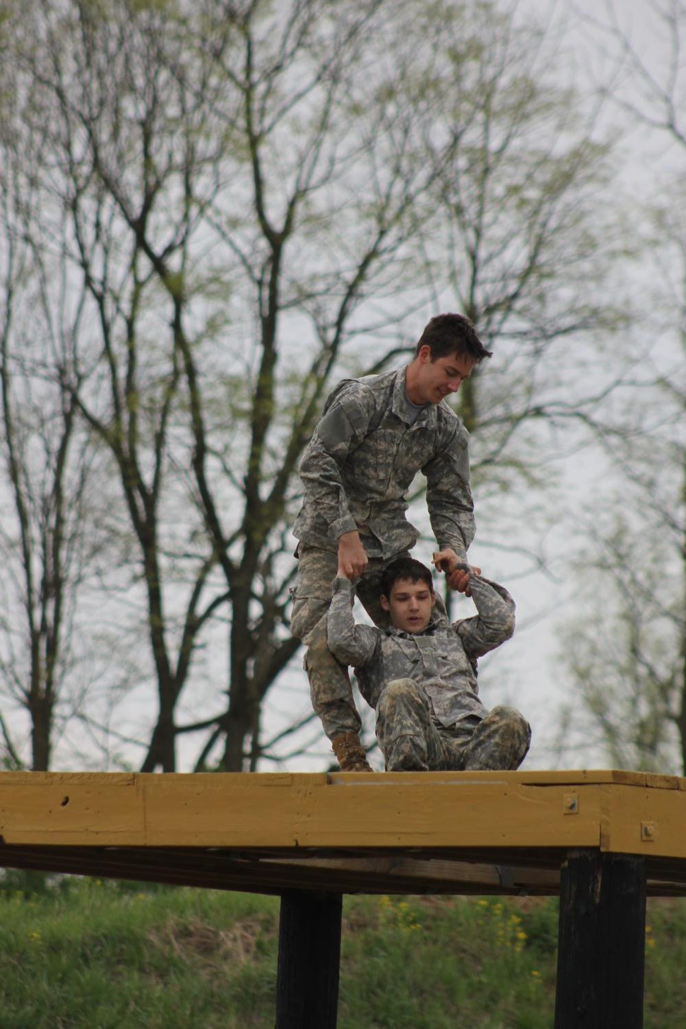 Junior Aaron Cooper assists sophomore Caleb Cooper on the obstacle course at the home raider meet