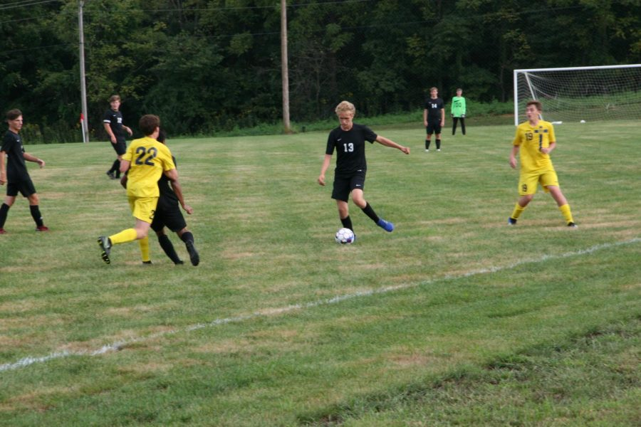Will Arras, senior, dribbles the ball in between two opponents.