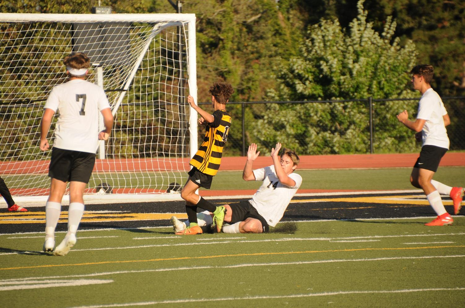 Number 14 Jedediah Dewey mid fall after stopping opponent from scoring a goal.