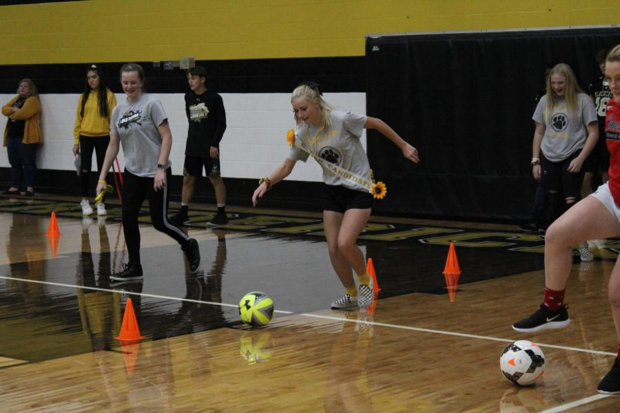 Senior, Alyssa Pierson, the representative for tennis dribbling the soccer ball, in the sports relay.